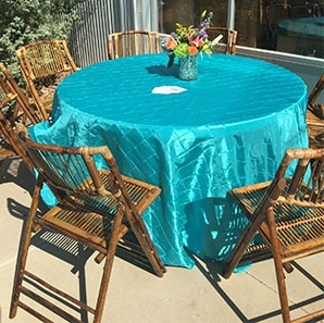Bamboo Chairs surrounding a round table covered with a turquoise pin tuck tablecloth.