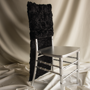 Black rosette chair cover on a silver colored Chiavari chair in front of a white back drop.