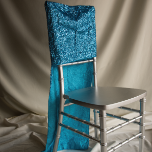 Blue sequined chair cover on a silver colored Chiavari chair in front of a white back drop.