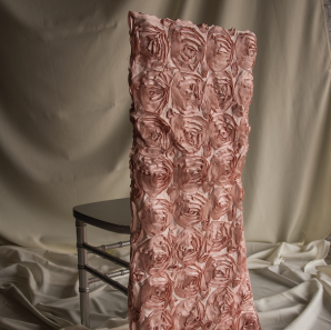 Blush rose colored rosette chair cover on a silver colored Chiavari chair in front of a white back drop.