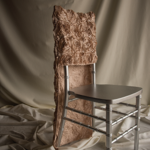 Champagne colored rosette chair cover on a silver colored Chiavari chair in front of a white back drop.