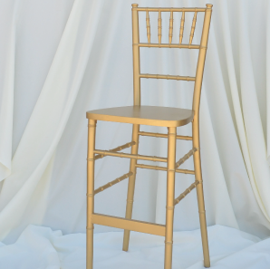 Gold colored Chiavari bar stool in front of  a white backdrop.