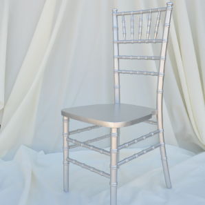 Silver colored Chiavari chair in front of  a white backdrop.