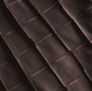 Close up of a chocolate brown pin tuck tablecloth.
