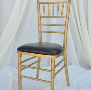 Gold colored chiavari chair with a black seat cushion in front of  a white backdrop.