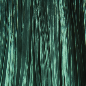 Close up of a forest green crinkled accordion tablecloth.