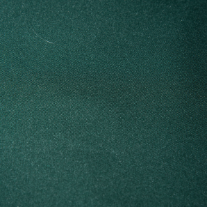 Close up of a forest green colored polyester tablecloth.