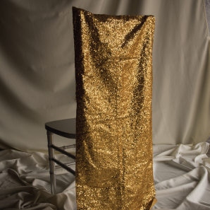 Gold sequined chair cover on a silver colored Chiavari chair in front of a white back drop.