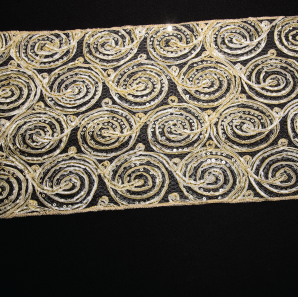 Close up of a gold swirled sequined table runner.