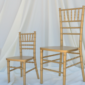 Kids gold Chiavari chair placed next to an normal sized gold Chiavair chair in front of  a white backdrop.