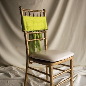 Front of a lime green colored chair sash tied into a bow on a silver chair.