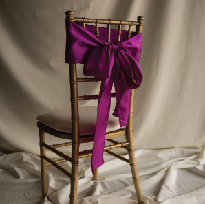 Back of a magenta colored chair sash tied into a bow on a silver chair.