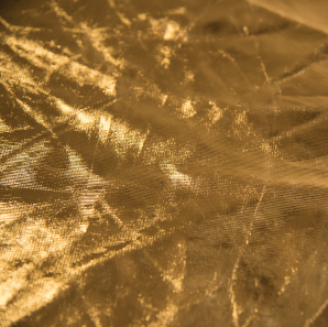 Close up of a metallic gold spandex tablecloth.
