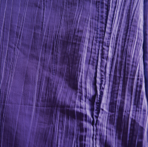 Close up of a purple crinkled accordion tablecloth.