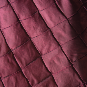 Close up of a purple pin tuck tablecloth.
