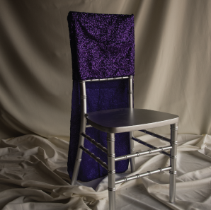 Purple sequined chair cover on a silver colored Chiavari chair in front of a white back drop.