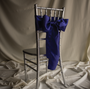 Royal blue chair sash on a silver Chiavari Chair in front of a white backdrop.