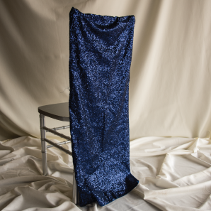 Royal blue sequined chair cover on a silver colored Chiavari chair in front of a white back drop.