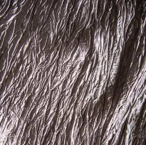 Close up of a silver colored crinkled accordion tablecloth.