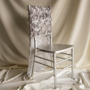 Silver rosette chair cover on a silver colored Chiavari chair in front of a white back drop.