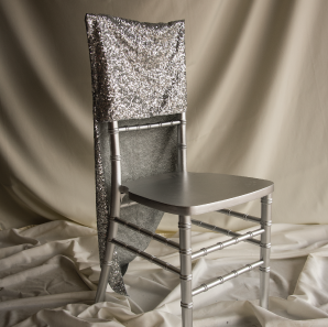 Silver sequined chair cover on a silver colored Chiavari chair in front of a white back drop.