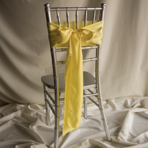 Back of a yellow chair sash tied into a bow on a silver chair.