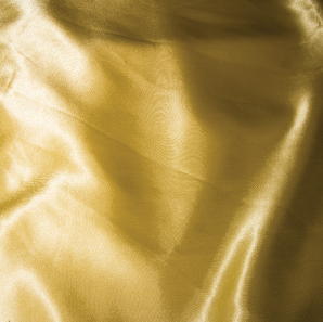 Close up of a yellow silk tablecloth.