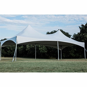White 40ft by 40ft tent set up in a large grass field with trees in the background.